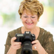 Постер, плакат: Retired woman viewing pictures on camera