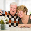Senior couple using cell phone at home — Stock Photo