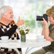 Senior wife taking a photo of her husband — Stock Photo