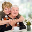 Retired couple hugging at home — Stock Photo