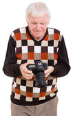 Senior man reviewing pictures on camera — Stock Photo