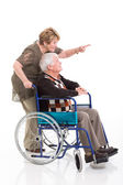 Senior woman behind disabled husband and pointing — Stock Photo