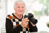 Elderly man holding a SLR camera — Stock Photo