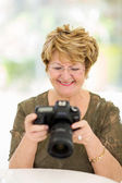 Retired woman viewing pictures on camera — Stock Photo