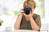 Senior woman shooting pictures — Foto Stock