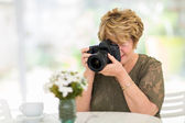 Senior woman photographing flowers — Stock Photo