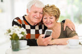 Elderly couple using smart phone — Stock Photo
