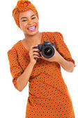 Young african woman holding a digital SLR camera — Stock Photo