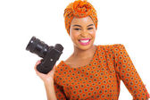 African woman holding a digital SLR camera — Stock Photo