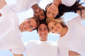 Group of friends in a circle looking down — Stock Photo