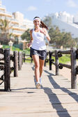 Young woman jogging at the beach — Stock Photo