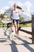 Woman jogging with her dog — Stock Photo