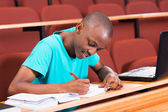 Student writing classwork — Stock Photo