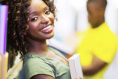 Smiling curly student in library — Stock Photo