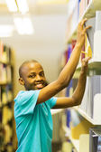 Student looking for books in library — Stock Photo