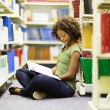 Student sitting on the floor in library — Stock Photo