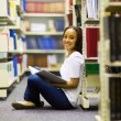 Girl sitting on the floor in library — Stock Photo