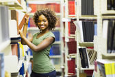 Curly college student in library — Stock Photo