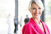 Middle aged businesswoman in pink blazer — Stock Photo