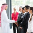 Businessman handshaking with his employees — Stock Photo