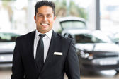 Car salesman in showroom — Stock Photo