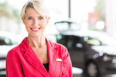Senior woman in car dealership — Stock Photo