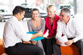 Car dealer explaining contract to buyers — Stock Photo