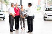 Vehicle salesman explaining contract to family — Stock Photo