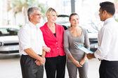 Car salesman talking to family — Stock Photo