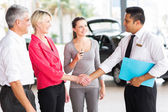 Woman handshaking with consultant after buying a car — Stock Photo