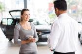 Car salesman talking to young woman — Stock Photo