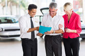 Mature couple buying a new car — Stock Photo