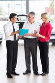 Middle age couple buying a car — Stock Photo