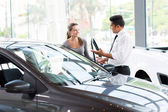 Vehicle dealer showing new car — Stock Photo