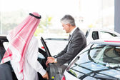 Man getting in a car for test drive — Stock Photo