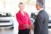 Mature woman handshaking with car dealer — Stock Photo