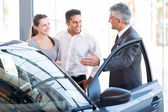 Mature salesman with a couple — Stock Photo