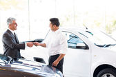 Salesman handing over car key — Stock Photo