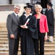 Graduate standing with parents at graduation — Stock Photo #42474493
