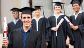Graduate with classmates holding his diploma — Stock Photo