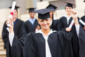 Graduate with outstretched arms holding her certificate — Stock Photo