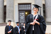 Female graduate wearing graduation gown — Stock Photo