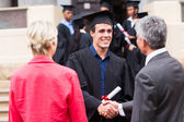 Male graduate handshaking with his father — Stock Photo