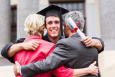 Graduate hugging his parents — Stock Photo