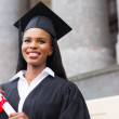 Female graduate with diploma outside college — Stock Photo #42481605