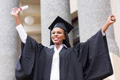 Female graduate with outstretched arms — Stock Photo