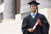 Graduate standing in front of university — Stock Photo