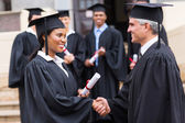Afro american graduate handshaking with dean — Stock Photo