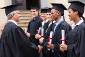 Professor handshaking with graduates — Stock Photo