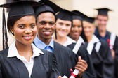 Multicultural university graduates standing in a row — Stock Photo